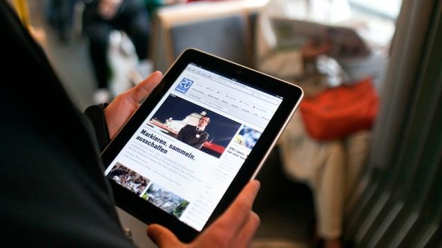 Blick auf ein Tablet, das eine Person in der Hand hält, aufgerufen ist die Webstie von 20min.ch.