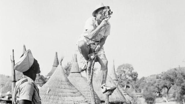 Ein Kameramann sitzt in Afrika auf einem dünnen Bäumchen, um von oben filmen zu können.