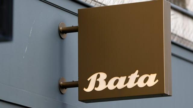 """Braunes Schild mit der Aufschrift """"Bata"""" ragt aus einer Hauswand eines Schuhgeschäfts"""