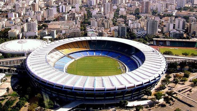 Blick auf das Stadion, hinter dem Hochhäuser in die Höhe ragen.