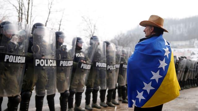Eingehüllt in die Flagge Bosnien-Herzegovinas steht ein demonstrierender Veteran der Übermacht der Polizei gegenüber.
