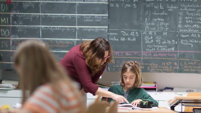 Eine Lehrerin beugt sich zu einem Jungen mit halblangen Haaren, der an einem Pult sitzt.