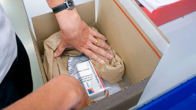 Zwei Frauenhände verpacken ein Medikament in eine Schachtel.