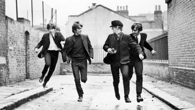 Vier Männer rennen durch eine Strasse
