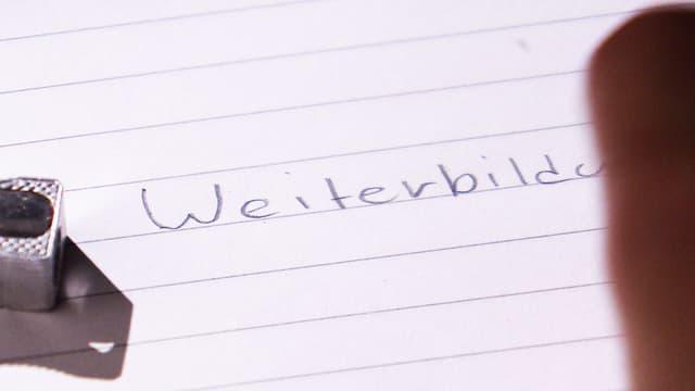 Das Wort Weiterbildung wird mit Bleistift auf Linienpapier geschrieben