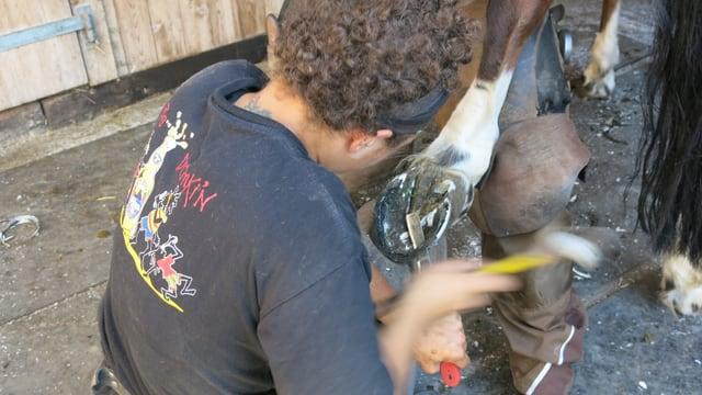 Melanie Schufaisl bearbeitet einen Huf mit Hammer und Messer.