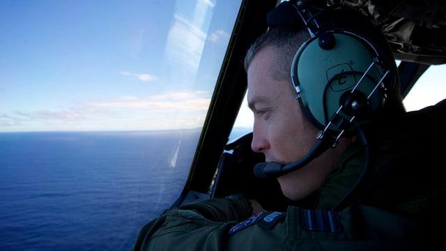 Pilot eines neuseeländischen Suchflugzeugs schaut aus dem Fenster aufs Meer.