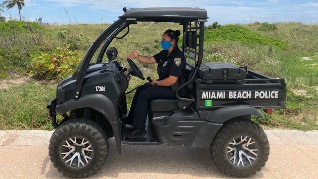 Polizistin in einem Polizeigefährt, sie trägt eine Hygienemaske.