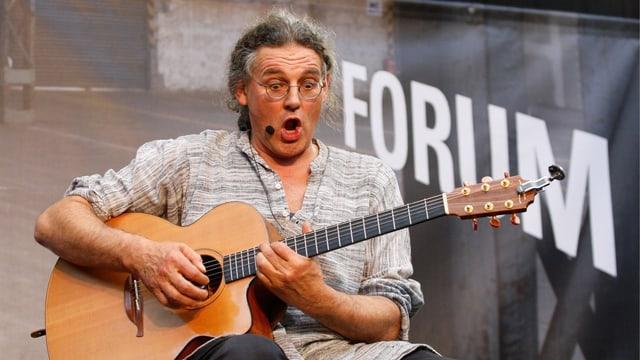 Linard Bardill sitzt mit Gitarre auf Stuhl und singt.