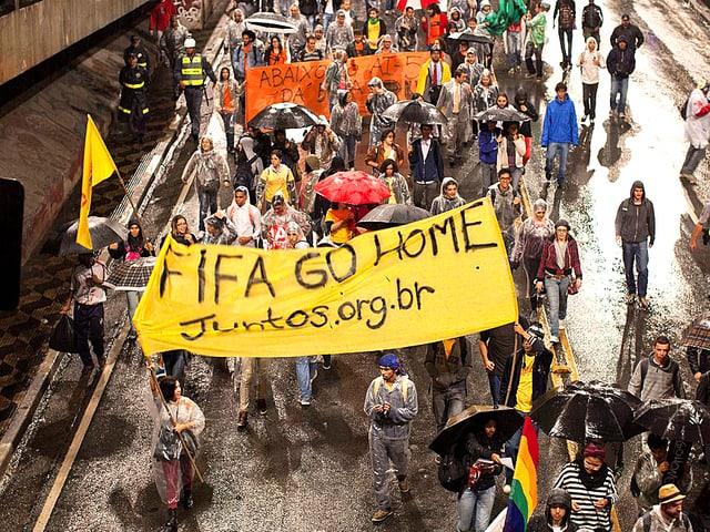 Brasilianer demonstrieren. SIe tragen ein Banner mit der Aufschrift «Fifa go home».
