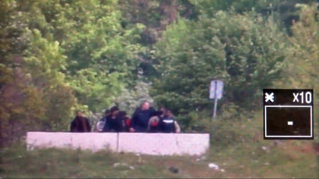 Grenzbeamter mit Gruppe von Flüchtlingen