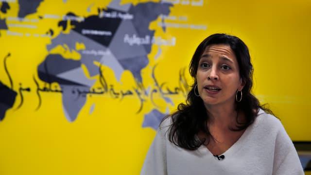 Lynn Maalouf vor einer Weltkarte.