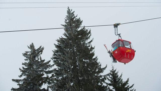 Eine kleine rote Seilbahnkabine in Les Diableretsin den Waadtländer Alpen vor grauem Himmel und drei schneebestäubten Tannenspitzen.