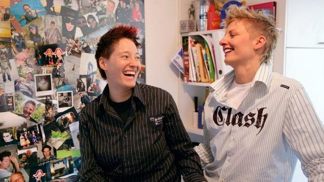 Zwei lesbische Frauen stehen in der Küche und lachen sich an