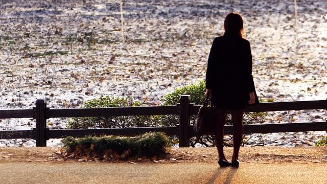 Eine Frau steht am Zaun vor einem Teich.