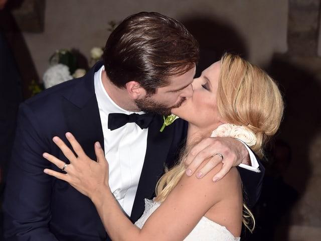 Ein Bräutigam küsst die blonde Braut in Weiss.