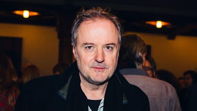 Das Haupt von Filmregisseur Stefan Haupt zwischen zwei Deckenleuchten.