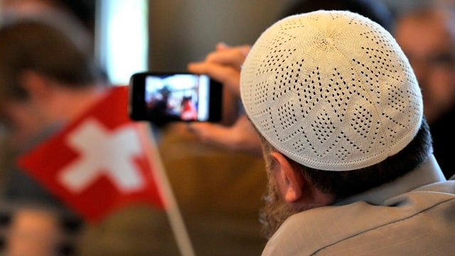 Ein Mann mit muslimischem Käppi schaut auf ein Smart Phone.