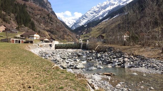 Ein Bach mit Steinen drin, links und rechts davon sind Berge.