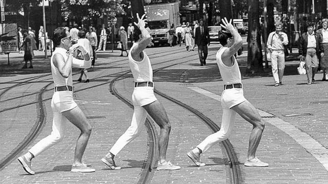 Drei Männer mit einbeinigen Hosen laufen auf Tramgleisen.