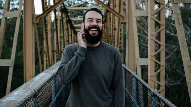 Mann lachend auf Brücke