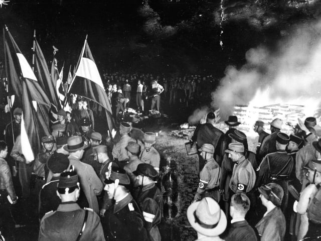Auf einer schwarz-weissen Fotografie stehen Männer in Uniformen und mit Fahnen um einen brennenden Haufen.