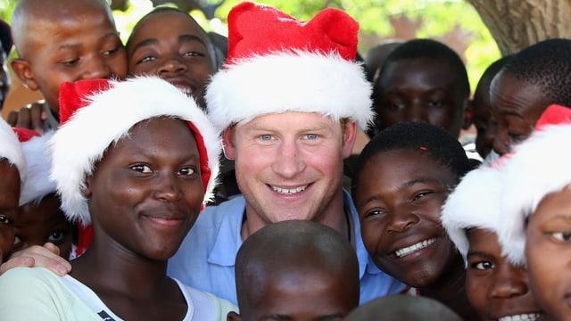 Prinz Harry trägt eine Nikolausmütze und wird umringt von Waisenkindern