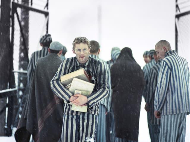 Ein Mann in einem gestreiften Overall trägt Bücher.