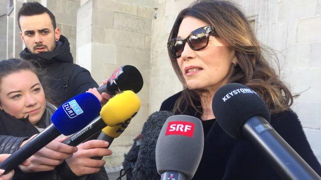 Frau mit Sonnenbrille hinter mehreren Mikrofonen