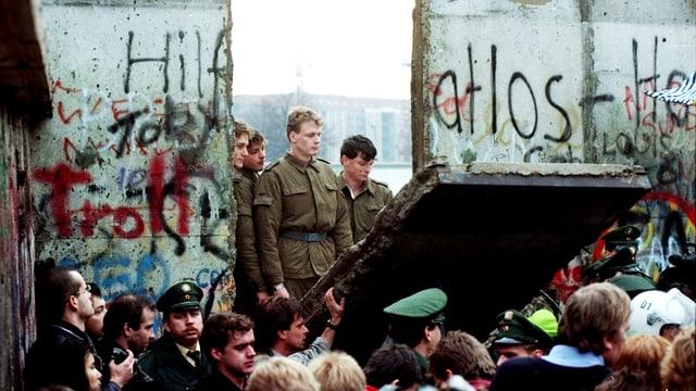 DDR-Grenzsoldaten schauen am 11. November 1989 durch ein Loch, das Jugendliche in die Berliner Mauer gestemmt haben.