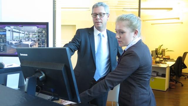 Mann und Frau in Anzug stehen vor Computer