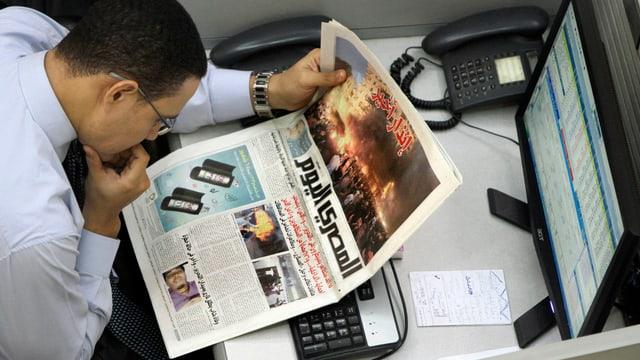 Ein Mann sieht sich das Titelblatt einer Zeitung an