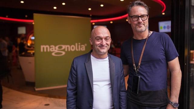 """Zwei Männer stehen vor einem """"Magnolia""""-Logo und schauen freundlich in die Kamera."""