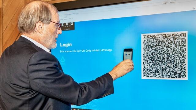 Dolfi Müller scannt mit seiner Handykamera einen QR-Code.