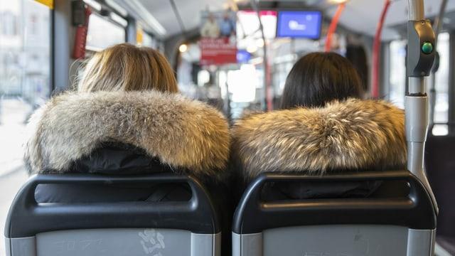 Duas dunnas en in bus portan giaccas cun pail.