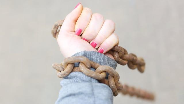 Eine Frauenhand in Ketten.