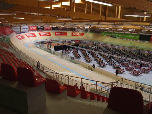 Blick in den Innenbereich. Eine Rundbahn, die im Oval angelegt ist. In der Mitte mehrere Tische mit Stühlen, alles ist bereit für die grosse Eröffnung. Die Bahn ist hellbraun, die Sitzplätze rundherum rot. Auf der Bahn sind mehrere Werbeaufdrucke zu sehen, unter anderem von der Veloherstellerin BMC.