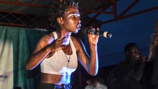 Eine junge schwarze Sängerin auf einer Festivalbühne.