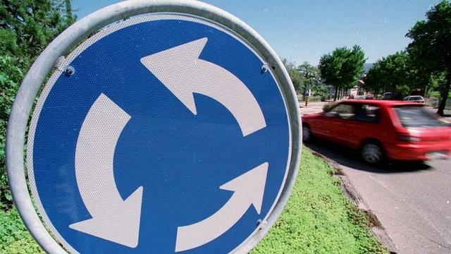 Verkehrsschild Kreisel im Vordergrunfd, dahinter sieht man ein rotes Auto, das den Kreisel befährt.