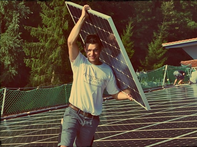 Fabian Dubach trägt eine Sonnenkollektoren-Installation.