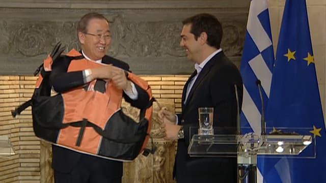Ban Ki-Moon rudert in der Schwimmweste mit den Armen, Alexis Tsipras grinst dazu.