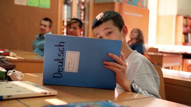 Ein Junge schaut in einer Schulklasse konzentriert in ein blaues Deutsch-Heft.