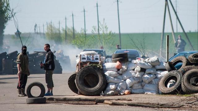 Zwei Männer sehen neben brennenden Autoreifen und Sandsäcken.