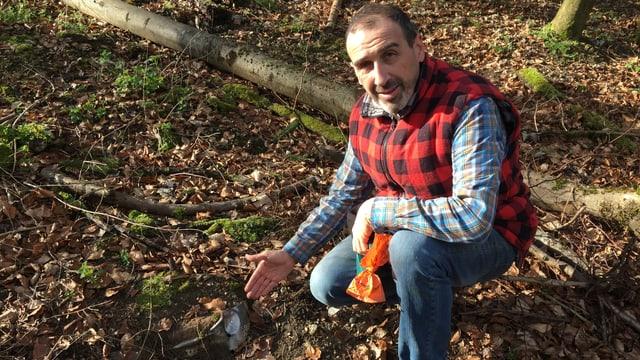 Marco Agostini sitzt im Wald und zeigt auf Abfall