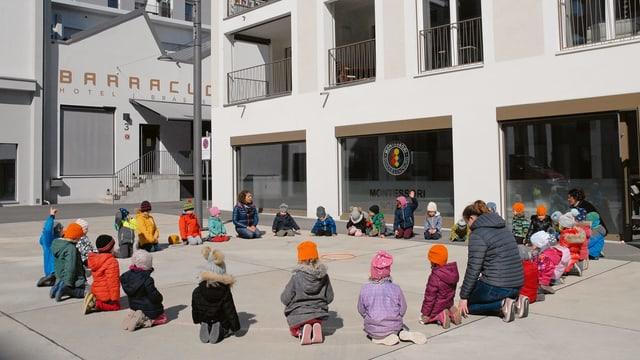 Kinder der Montessori-Schule sitzen im Kreis. Daneben sieht man das trendige Restaurant «Barracuda».