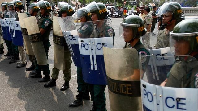 Kambodschaniesche Polizisten stehen mit Schild und Helm in einer Reihe.