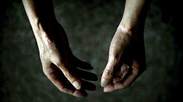 Hände einer Person, die offenbar kopfüber hängt.