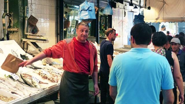 Ein Marktschreier preist seine Fische an.