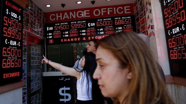 Menschen stehen vor einem Währungsbüro und studieren die Kurse.