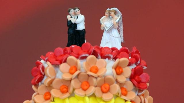 Regenbogentorte mit zwei gleichgeschlechtlichen Paaren auf der Spitze.
